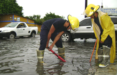 Cozumel firemen work to open a clogged drain